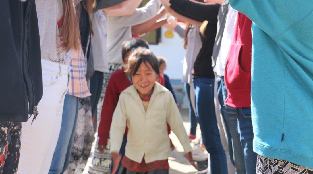 チャイルドケアボランティアのトンネルを進むネパールの子供たち